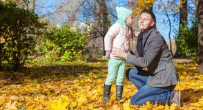 Little girl kissing her father in autumn park Royalty Free Stock Images