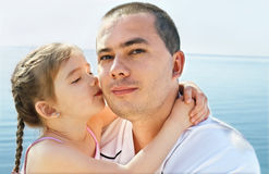 Little girl kissing her father on beach vacation Royalty Free Stock Images