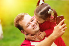 Little girl kissing her father on cheek while taking selfie Royalty Free Stock Photo