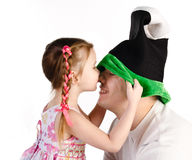 Little girl kissing her father in funny cap isolated Royalty Free Stock Image