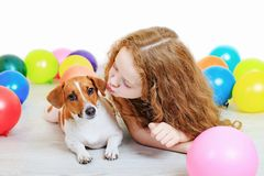 Little girl kissing with her jack russell terrier in birthday pa Royalty Free Stock Photo