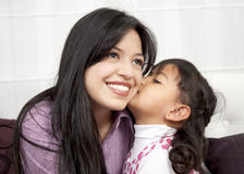 Little girl kissing her mommy. In the home Royalty Free Stock Photos