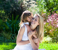 Little girl kissing her mother stock photo