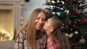 Little girl kissing her mother at Christmas stock video