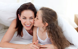 Little girl kissing her mother lying on bed Stock Photography