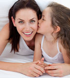 Little girl kissing her mother lying on bed royalty free stock photos