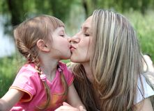 Little girl kissing her mother in  park Stock Photo