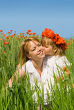 Little girl kissing her mother on the poppy field Royalty Free Stock Photography