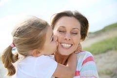 Little girl kissing her mother Stock Photos