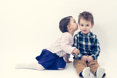 Little girl kissing her older brother on the cheek Stock Photo