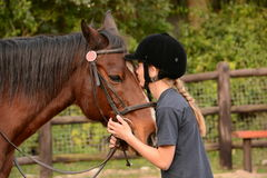 Little girl kissing her pony. Outdoor side view of a preteen Caucasian girl rider holding and kissing her dark bay pony Stock Photo