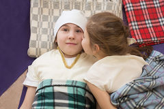 Little girl kissing her sister lying on the plaids Royalty Free Stock Images