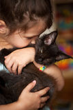 Little girl kissing kitten Maine Coon Royalty Free Stock Photos