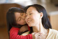 Little girl kissing mother. Asian daughter hugging and kissing mother Royalty Free Stock Images