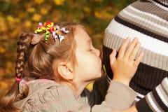 Little girl kissing mother's pregnant belly Stock Image