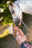 Little girl kissing pony. Cute little girl dressed in cowgirl clothes kissing her pet pony on the nose Royalty Free Stock Photo
