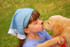 Little girl kissing puppy Stock Photography