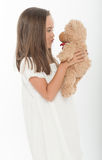 Little girl kissing teddy bear Stock Images