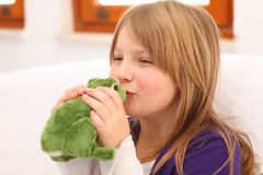 Little girl kissing toy frog on sofa Stock Photo