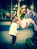 Little girl kissing a unicorn. Baby girl kissing toy unicorn Royalty Free Stock Photos