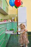 Little girl on kitchen Stock Image