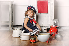 Little girl in the kitchen. Of cookware Stock Photos