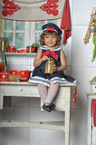Little girl in the kitchen. Of cookware Stock Images