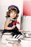 Little girl in the kitchen. Of cookware Stock Image