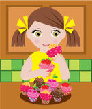 Little girl in kitchen with cupcakes Royalty Free Stock Photo