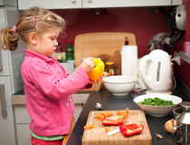 Little girl in the kitchen stock photography