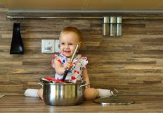 Little girl in the kitchen with a ladle and a pot royalty free stock photos