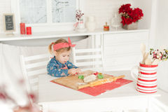 Little girl in the kitchen making cookies. Little girl baking cookies in the kitchen stock photo