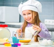 Little girl in the kitchen preparing cookies Stock Photo