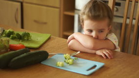 Little girl in the kitchen. She is upset, crying, hiding her face. Not hungry. Refuses to eat. Childish whims. HD stock video