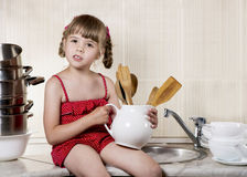 Little girl in kitchen Stock Photos