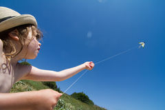 Little girl with kite. Wide angle portrait of a little girl with white wicker hat raising a small kite on the beach and holding it by the string against a blue Royalty Free Stock Photography