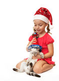 Little girl with kitten in Christmas hats. Royalty Free Stock Photos