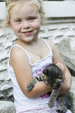 Little girl and kitten. Striped kitten resting in the arms of a little girl stock photography