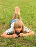 Little girl with a kitty. Barefoot girl - little kid lying on meadow with a small black kitty Stock Photo