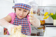 Little girl kneading dough Stock Images