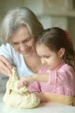 Little girl kneading dough with grandmother Royalty Free Stock Photo