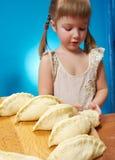 Little girl kneading dough Stock Photography