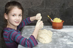 Little girl kneads the dough Royalty Free Stock Image