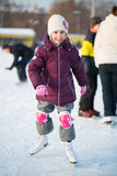 Little girl in knee pads skating at the rink. In winter royalty free stock photography