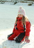 Little girl kneeing on iced pond Royalty Free Stock Image