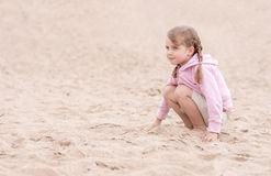 Little girl kneeling on the sand and looking ahead Stock Photos