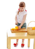 Little girl with a knife cuts vegetables Royalty Free Stock Images