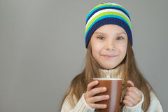 Little girl in knitted cap drinking tea Stock Images