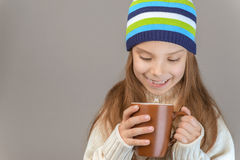 Little girl in knitted cap drinking tea Royalty Free Stock Image