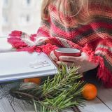 A little girl in a knitted sweater sitting on a windowsill and reading a book. A winter photo of a little girl in a knitted sweater sitting on a windowsill and Stock Photography